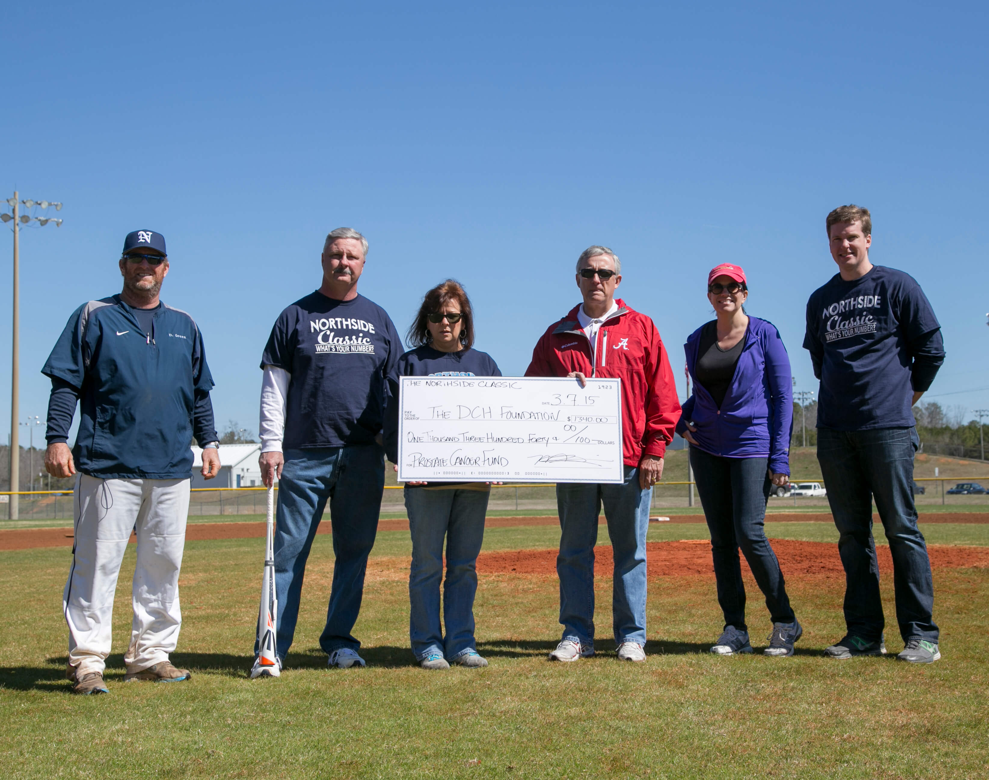 6 people standing with a large check